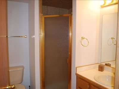 Bottom floor guest bathroom and shower -- also contains the washer & dryer