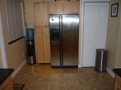 New Jenn Aire fridge, 5 gallon water jug and pantry cabinets.
