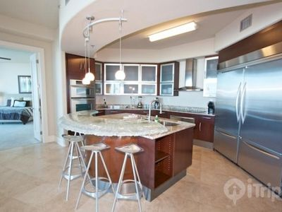 fully equipped kitchen with 3 bar stools