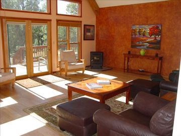 Spacious living room with comfy leather chairs and pellet stove