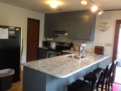 Updated kitchen w/ brand new appliances, large granite island, and 3-seat bar