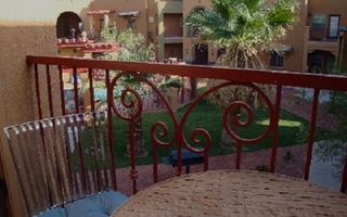 Las Cruces condo photo - Balcony and dining table with view of the pool courtyard