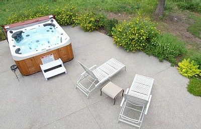 Hot tub sits six and shrubs around patio.