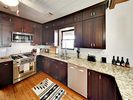 Kitchen - The modern kitchen is equipped with stone countertops and a full suite of stainless steel appliances.