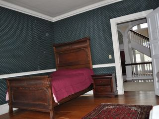 Newport chalet photo - Antique, 100 year old bed, see winding stair case in hall.