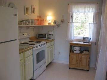 Kitchen with slight view of cove behind cottage