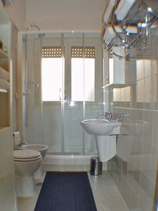 The bathroom offers a large shower with a bench and lots of thick white towels