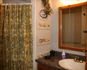 Interesting decor, wrought iron towel racks, shower, vanity, hair dryer.