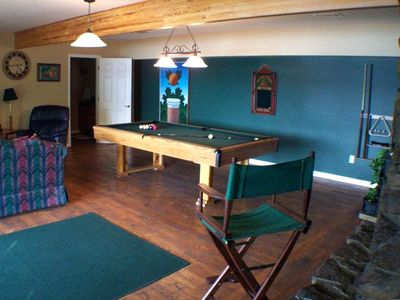 Gameroom with pool table, stone fireplace and sliding glass door to deck