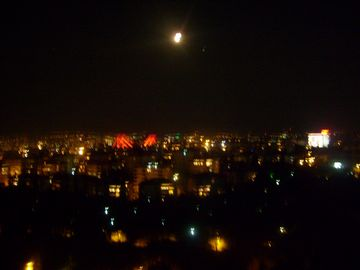 Night view from the balcony with the full moon, Bosphorus bridge lit up in red