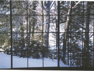 Saint-Sauveur cabin photo - winter view from the dining room window. The lake is seen through the trees.