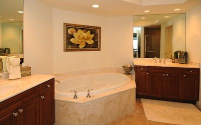 Master Bath has split vanities with bath and shower (relected in mirror).