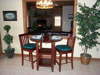 Romantic dining area with pass through to fireplace and television. - Pigeon Forge cabin vacation rental photo