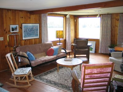 The Sow's Ear, a Franconia Notch Vacations Property - The Living Area is accented with lots of natural light and wood with those 2 windows looking straight at Mount Lafayette & Cannon Mountain.