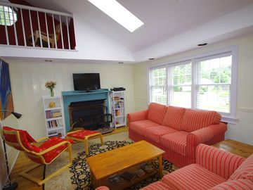 Open, airy living room with fireplace, HDTV, DVR, BRD/DVD/CD player.