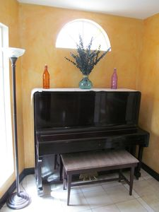 Upright piano sounds great in the game room with tile floors