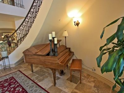 Spiral staircase winds above this antique piano in foyer