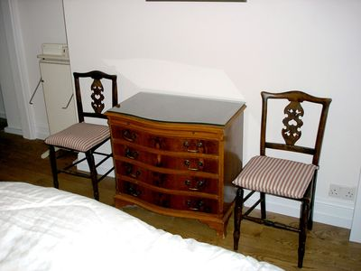 CHEST OF DRAWERS with two bedroom chairs and a trouser press.