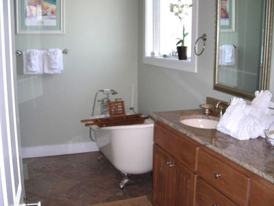 Relax in the antique tub next to the ceramic tile shower in the Master Bath
