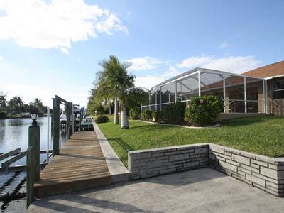 Captains Walk - outside patio, dock and boat lift along canal.