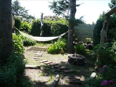 Backyard where you will find a comfortable hammock and fire pit.