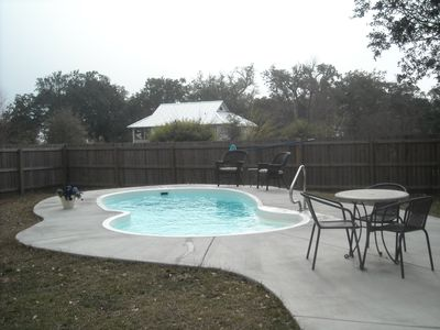 Pool area with small dining set and 2 wicker chairs with cushions