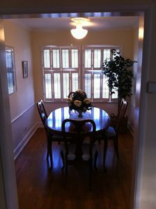 A beautiful dining room with windows and a classic wooden table that seats 4.