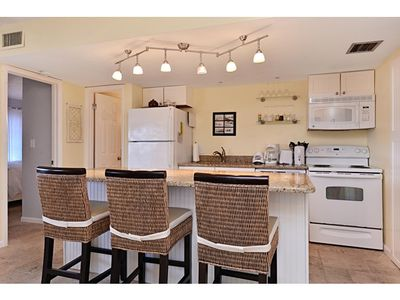 Granite counter, bar stools and appliances make a great gathering place.