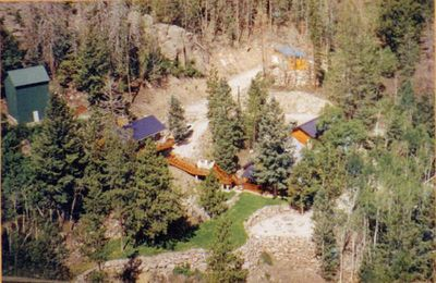 Aerial photo of property. Bunkhouse is on left, main cabin and garage is right.
