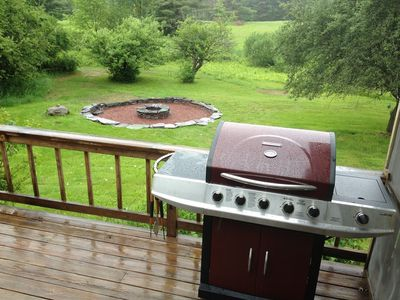 The new 5 burner BBQ and large stone fire pit in the rear yard.