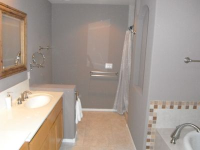Master bath with soak tub and walk in shower around the corner.