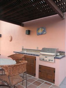 Barbecue center with sink, patio table with 4 chairs under ramada