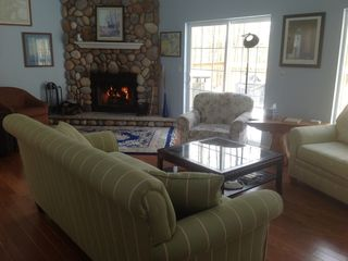 Great room with cozy stone fireplace and two sliders to 40-foot deck