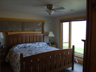 Master bedroom with king bed and ceiling fan. Windows open and face N, S, and W.