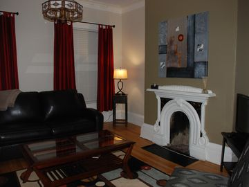 Living room (fireplace with original mouldings), taken from the kitchen