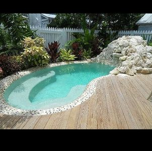 Beautiful shared heated pool with coral waterfall.