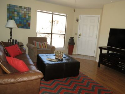 Enter to a brightly furnished living room with a flat screen TV.