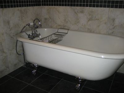 Claw foot bathtub, this bathroom also has a shower and heated tile floors.
