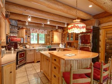 Large kitchen w/ Heartland Vintage style appliances and island with bar seating.