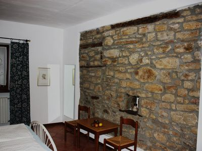 Stone wall in the bedroom of the apartment 2