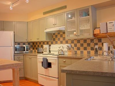 Wide kitchen and bar area is fully appointed with all useful appliances and more
