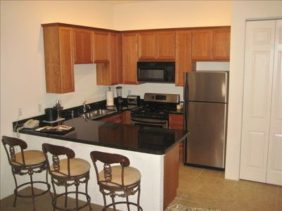 Full kitchen with bar chairs, washer and dryer