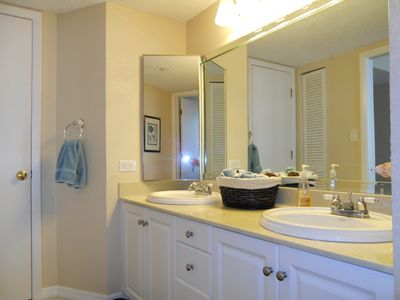 walk-in closet and twin sinks in updated master bath