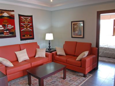 Bright living room with recessed direct lighting tray ceiling. Lamps provide reading lights.