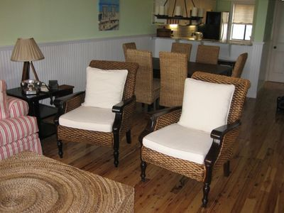 Comfy wicker chairs with dining area and kitchen beyond