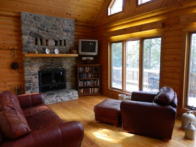 Living room with comfortable furniture, fireplace and windows overlooking lake