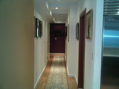 Long hallway separates living room/kitchen from bedrooms