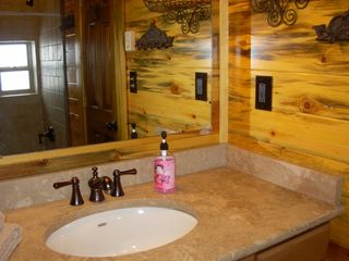 Kalispell barn photo - Lovely bath, travertine counter, tiled tub & shower seen in mirror