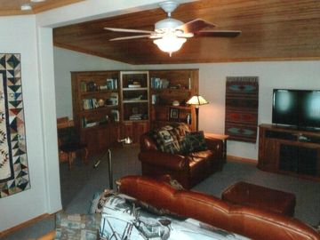Living room includes library of books and games, two seating areas.