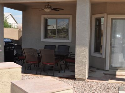 Back patio with seating for six, ceiling fan and gas grill.